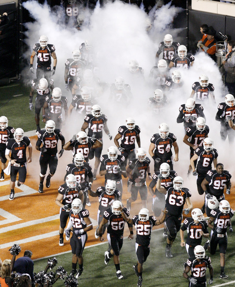 Photo - The OSU football team takes the field before the college football game between Oklahoma State University (OSU) and the University of Colorado (CU) at Boone Pickens Stadium in Stillwater, Okla., Thursday, Nov. 19, 2009. Photo by Bryan Terry, The Oklahoman