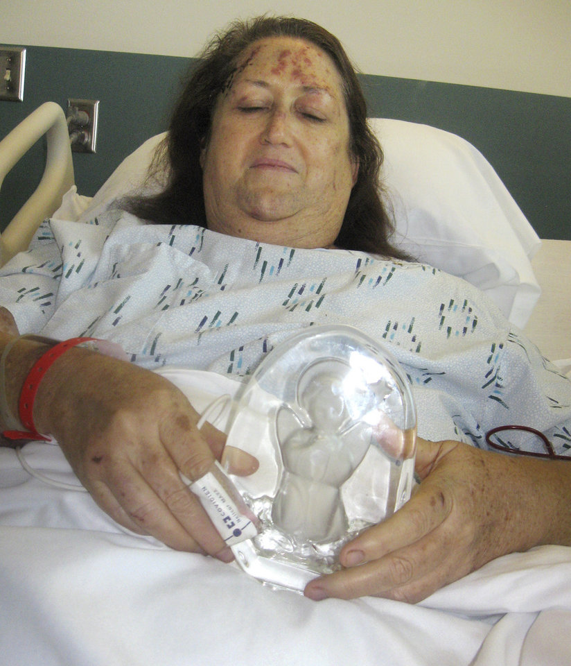 Jerrie Bhonde, 57, holds an angel figurine her daughter found near their home, in her hospital bed at Integris Southwest Medical Center, 4401 S. Western in Oklahoma City. Her ill husband was ripped from her arms near Plaza Towers Elementary School on May 20. He was found dead a short distance from the couple\'s home. Jerrie is covered in cuts and bruises but remained alert during the tornado, even able to describe the moment her husband was sucked into the tornado while she stayed put in an interior bathroom. The couple collected angels. Photo by Andrew Knittle, The Oklahoman