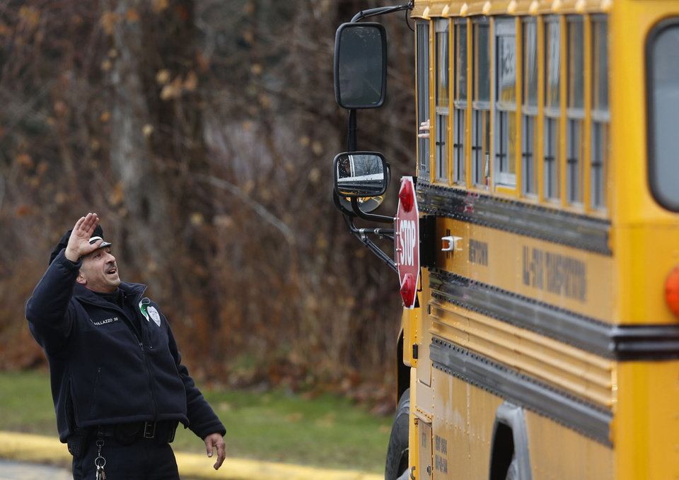 Photo - Easton police officer J. Sollazzo waves to returning children as their bus pulls into Hawley School, Tuesday, Dec. 18, 2012, in Newtown, Conn.  Classes resume Tuesday for Newtown schools except those at Sandy Hook. Buses ferrying students to schools were festooned with large green and white ribbons on the front grills, the colors of Sandy Hook. At Newtown High School, students in sweatshirts and jackets, many wearing headphones, betrayed mixed emotions.  Adam Lanza walked into Sandy Hook Elementary School in Newtown,  Friday and opened fire, killing 26 people, including 20 children, before killing himself.(AP Photo/Jason DeCrow)