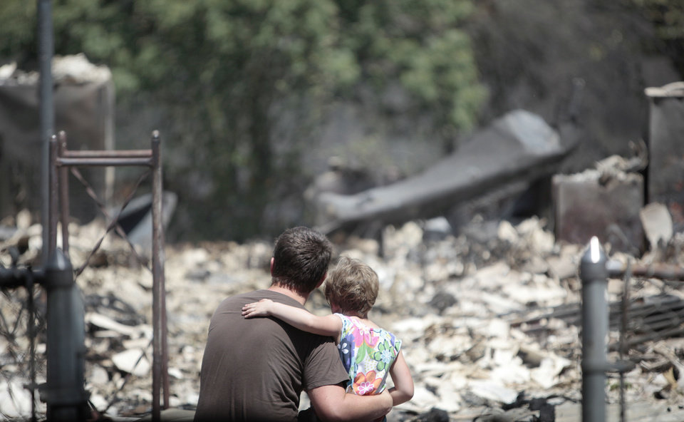 Photo - Jonathan Bell looks Sunday at what is left of a relative's home with his daughter, Abigail, 5, in  the Oak Grove community near Drumright after wildfires moved through the area Saturday. Photo by Sarah Phipps, The Oklahoman  SARAH PHIPPS - THE OKLAHOMAN