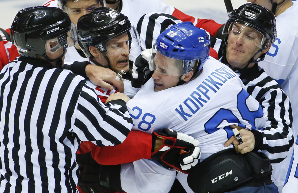 Photo - Referees break up a scuffle between Austria forward Daniel Welser (20) and Finland forward Lauri Korpikoski in the third period of a men's ice hockey game at the 2014 Winter Olympics, Thursday, Feb. 13, 2014, in Sochi, Russia. (AP Photo/Mark Humphrey)