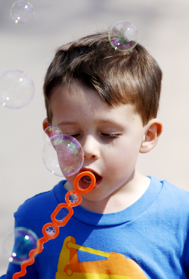 Photo - Liam Arguello, 4, blows bubbles at Open Streets OKC, along NW 23rd Street between Robinson and Western, Sunday, March 22, 2015. Photo by Doug Hoke, The Oklahoman