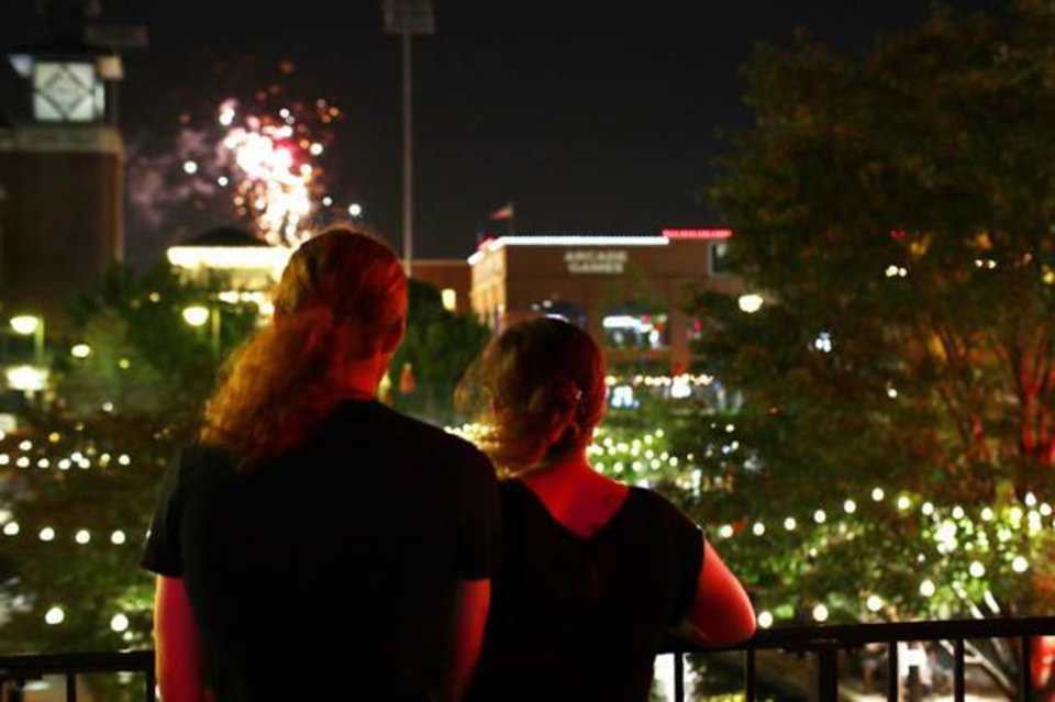 Photo -  A couple watch the fireworks after a Dodgers baseball game from the S Oklahoma Avenue bridge along the Bricktown Canal. [PHOTO BY DOUG HOKE, THE OKLAHOMAN]