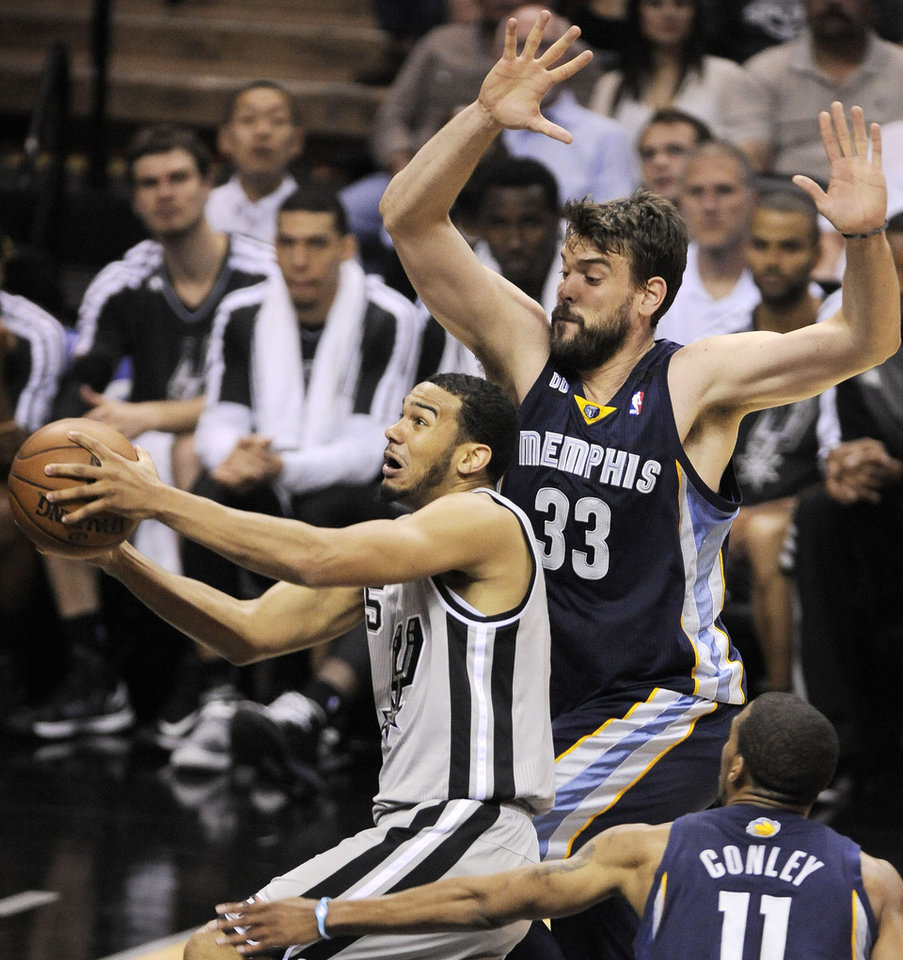 Photo - San Antonio Spurs' Cory Joseph, left, drives between Memphis Grizzlies' Marc Gasol, top, of Spain, and Mike Conley during the first half of Game 1 of the Western Conference final NBA basketball playoff series, Sunday, May 19, 2013, in San Antonio. (AP Photo/Darren Abate)