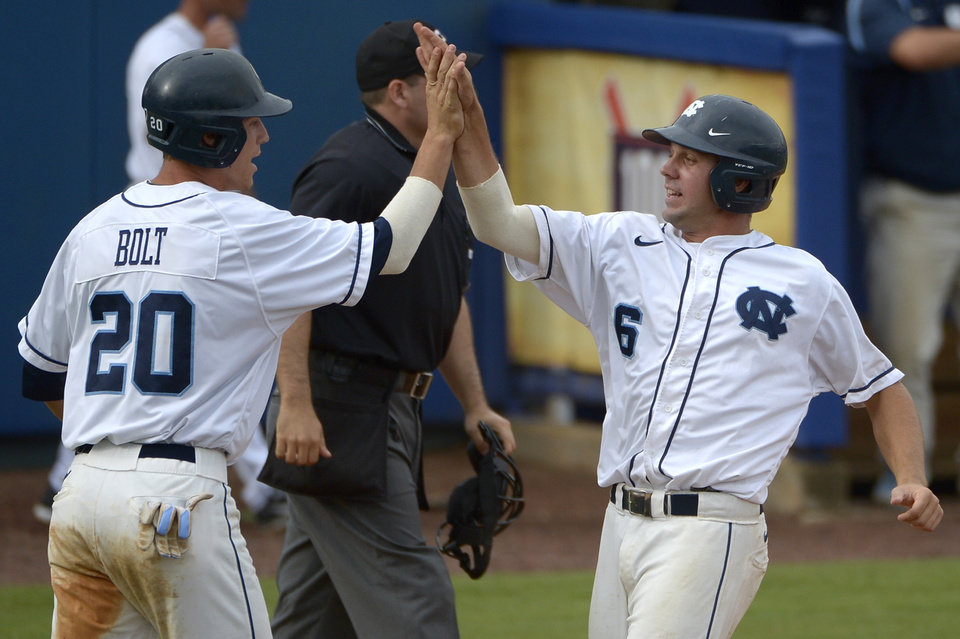 Photo - North Carolina's Skye Bolt (20) and Alex Raburn (6) score on a double by teammate Tyler Ramirez during the third inning of an NCAA college baseball regional tournament game against Florida in Gainesville, Fla., Saturday, May 31, 2014.(AP Photo/Phelan M. Ebenhack)