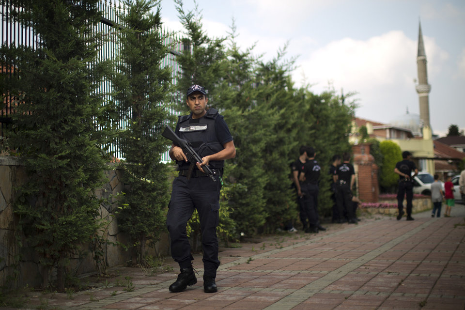 Photo - A police officer holds his weapon as he secures the area ahead of arrival of the Prime Minister Recep Tayyip Erdogan, who is the front-runner in Turkey's presidential election, in a poll station in Istanbul, Turkey, on Sunday, Aug. 10, 2014. Turks were voting in their first direct presidential election Sunday - a watershed event in Turkey's 91-year history, where the president was previously elected by Parliament. Prime Minister RecepTayyip Erdogan, who has dominated the country's politics for the past decade, is the strong front-runner to replace the incumbent, Abdullah Gul, for a five-year term. (AP Photo/Emilio Morenatti)