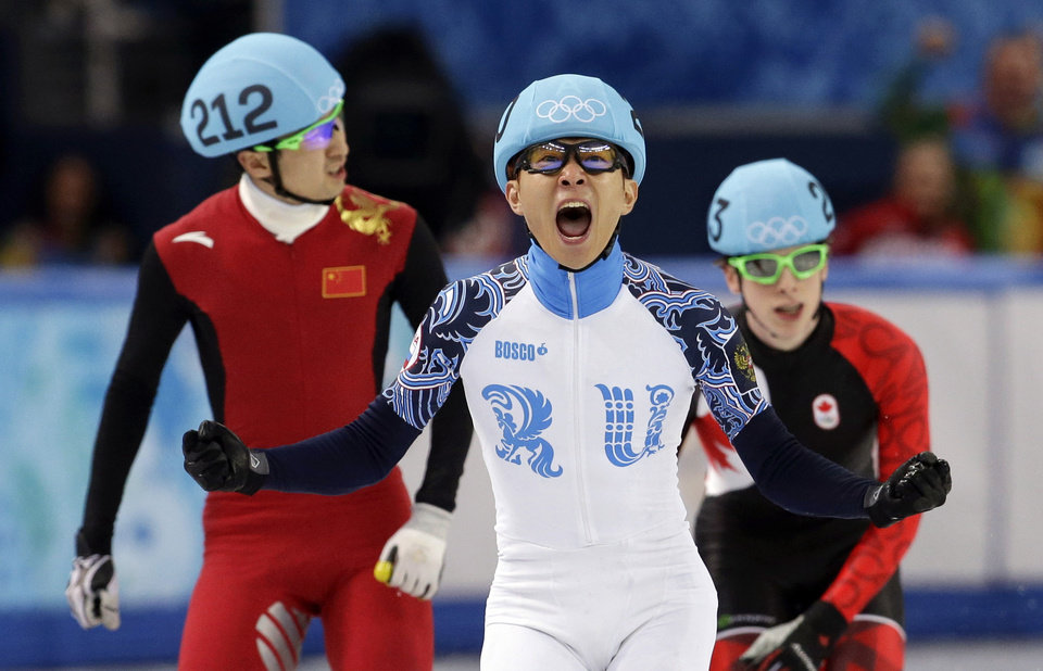 Photo - Victor An, center, of Russia, reacts as he crosses the finish line ahead of Wu Dajing, left, of China, and Charle Cournoyer of Canada in the men's 500m short track speedskating final at the Iceberg Skating Palace during the 2014 Winter Olympics, Friday, Feb. 21, 2014, in Sochi, Russia. (AP Photo/Darron Cummings, File)