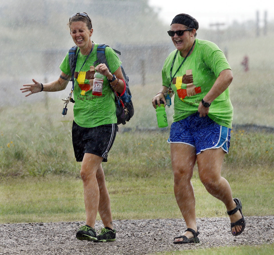 Camp leaders Stephanie Darden and Katherine Devonshire run between buildings in the rain at a summer camp for children with developmental disabilities called Camp Claphans at the J.D. McCarty Center on Wednesday, July 17, 2013 in Norman, Okla.  Photo by Steve Sisney, The Oklahoman