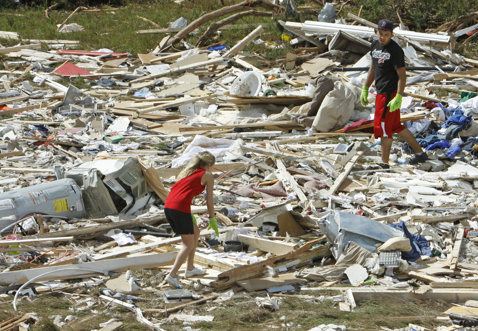 Photo - Breanna Bobbitt, 18, and Cameron Bickerstaff, 17 from Ninnekah, help April Winfrey salvage items from part of her manufactured home as residents cleanup following Tuesday's deadly tornado  on Wednesday, May 25, 2011, in Chickasha, Okla.  The home was pulled from concrete piers, split in two and the two halves landed 150 yards apart. Photo by Steve Sisney, The Oklahoman