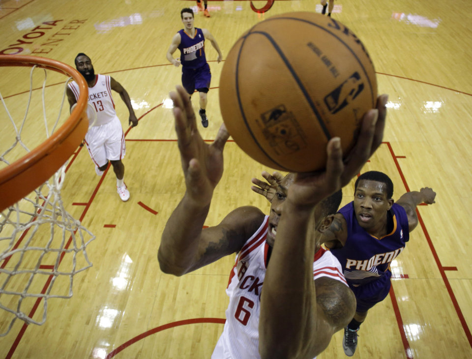 Houston Rockets' Terrence Jones (6) shoots as Phoenix Suns' Channing Frye, right, defends during the first quarter of an NBA basketball game Wednesday, Dec. 4, 2013, in Houston. (AP Photo/David J. Phillip)