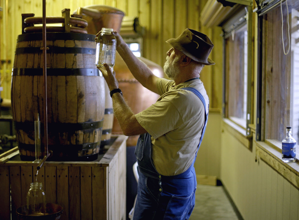 in this Friday, Nov. 16, 2012 photo, distiller Bob Suchke checks the clarity of a batch of genuine corn whisky before its tempered in the Dawsonville Moonshine Distillery, in Dawsonville, Ga. Distillers are making their first batches of legal liquor in this tiny Georgia town's hall, not far from the mountains and the maroon, orange and gold canopy of trees that once hid bootleggers from the law. (AP Photo/David Goldman)