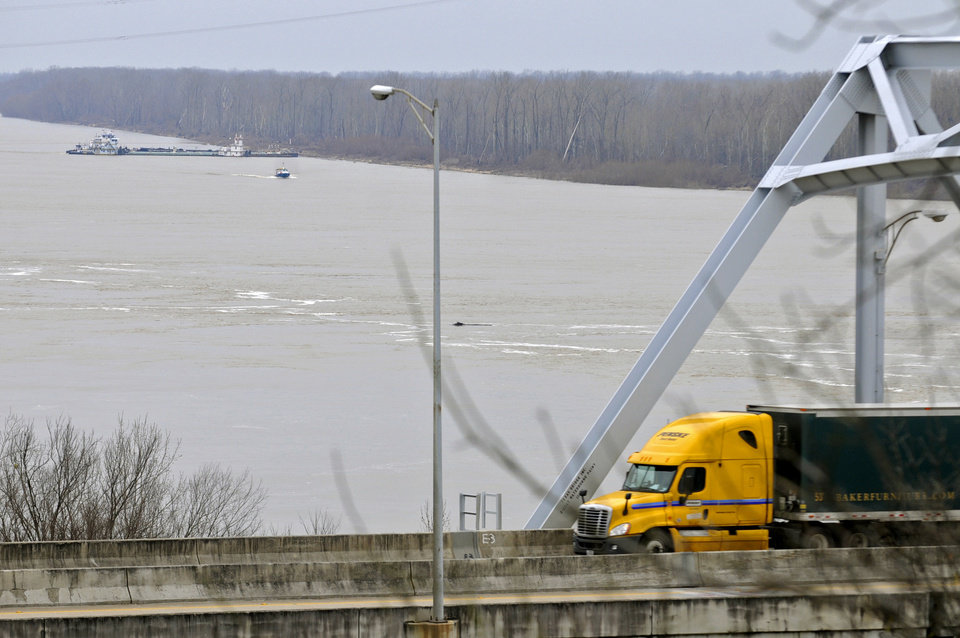 Photo - CORRECTS DATE TO JAN. 28, NOT JAN. 18 - The towboat Natures Way Endeavor, background, banks a barge against the western bank of the Mississippi River, Monday, Jan. 28, 2013 as an 18-wheeler crosses the Interstate 20 bridge. Cleanup crews with booms skimmed oily water from the Mississippi River Monday, a day after a barge with more than 80,000 gallons of oil struck a railroad bridge near Vicksburg, spreading a sheen of light crude that kept part of the waterway shut to ship traffic Monday, authorities said. (AP Photo/Eli Baylis)
