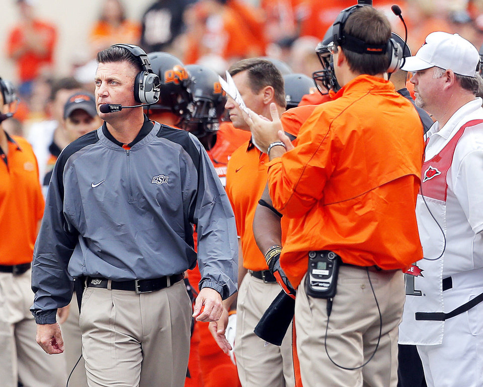 With the absence of an offensive coordinator, Oklahoma State coach Mike Gundy, left, has essentially been the leader in quarterback meetings.  Photo by Sarah Phipps, The Oklahoman
