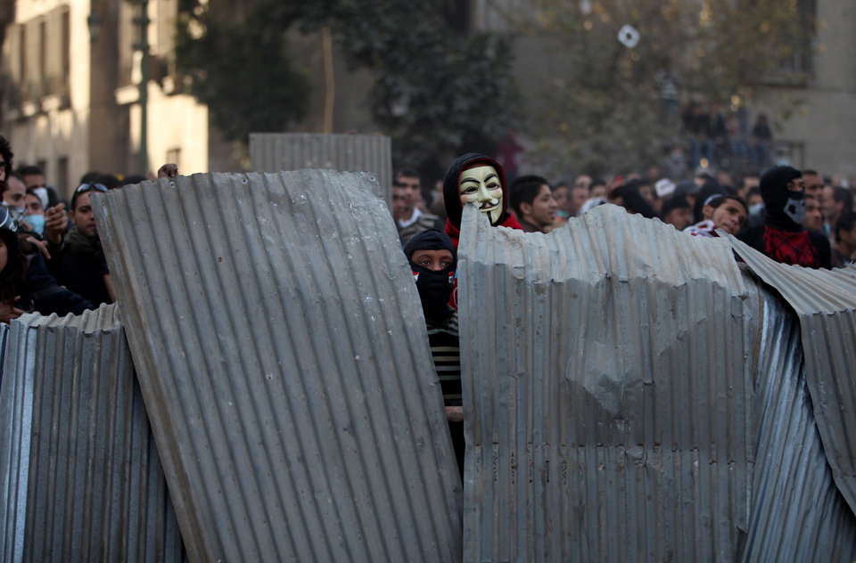 Egyptian protesters take cover as they clash with riot police, not seen, near Tahrir Square, Cairo, Egypt, Friday, Jan. 25, 2013. Youth activists and opposition groups have called for large rallies to mark the second anniversary of Egypt's Jan. 25, 2011 uprising that toppled long-time authoritarian leader President Hosni Mubarak. (AP Photo/Khalil Hamra) ORG XMIT: KH126