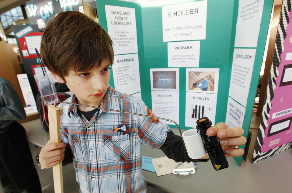 "Photo - Fourth-grader Matthew Kryvenia, 9, from Heritage Trails Elementary in Moore, shows off his flashlight holder invention, named the ""K Holder,"" during the Oklahoma Student Inventors Exposition held at Rose State College in Midwest City. Photos by Paul B. Southerland, The Oklahoman"