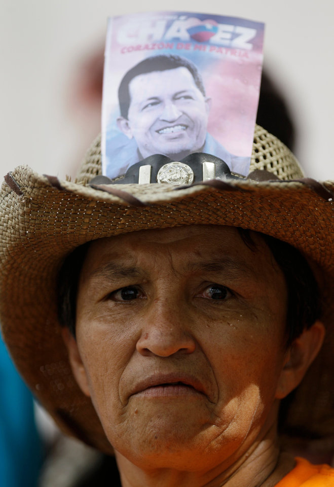 Photo - A supporter of Venezuela's President Hugo Chavez wears a hat decorated with a photograph of him outside the National Assembly in Caracas, Venezuela, Saturday, Jan. 5, 2013. Venezuelan lawmakers are meeting Saturday to select a new president of the National Assembly in a session that could give clues to the future of the country amid uncertainty about ailing Chavez. Just five days remain until Chavez's scheduled inauguration on Thursday and officials are suggesting the swearing-in could be delayed. (AP Photo/Fernando Llano)
