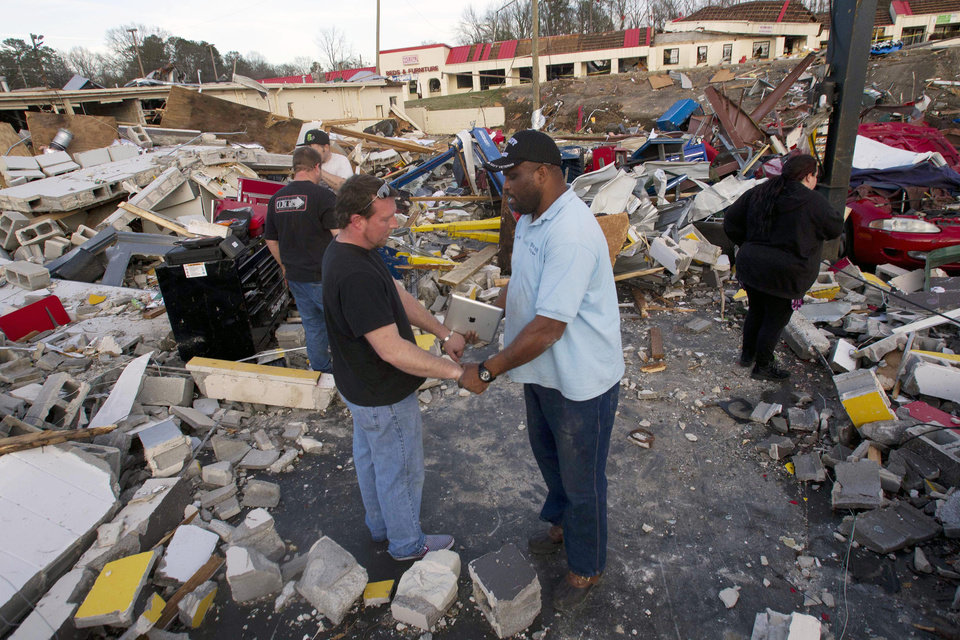 The Rev. Herman Henderson, right, prays with Brent Cherry in the middle of his destroyed business in Center Point, Ala., Monday, Jan. 23, 2012. Jefferson County sheriff's spokesman Randy Christian said the storm produced a possible tornado that moved across northern Jefferson County around 3:30 a.m., causing damage in Oak Grove, Graysville, Fultondale, Clay and Trussville.  (AP Photo/Dave Martin) ORG XMIT: ALDM119