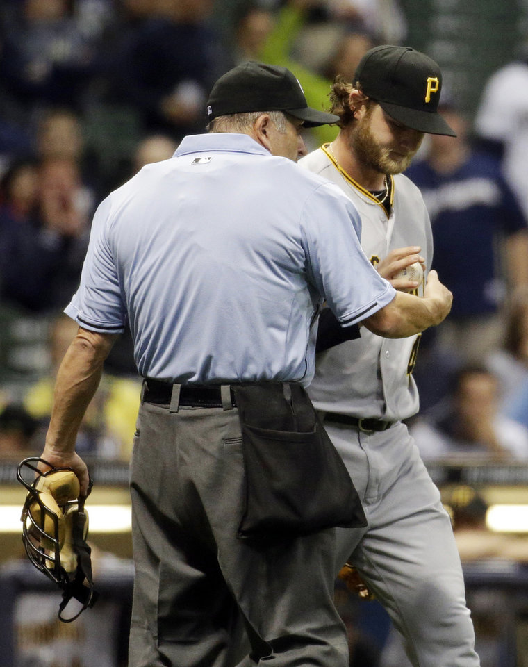 Photo - Home plate umpire Dale Scott talks to Pittsburgh Pirates starting pitcher Gerrit Cole, right, after Cole hit Milwaukee Brewers' Carlos Gomez with a pitch during the third inning of a baseball game Tuesday, May 13, 2014, in Milwaukee. (AP Photo/Morry Gash)