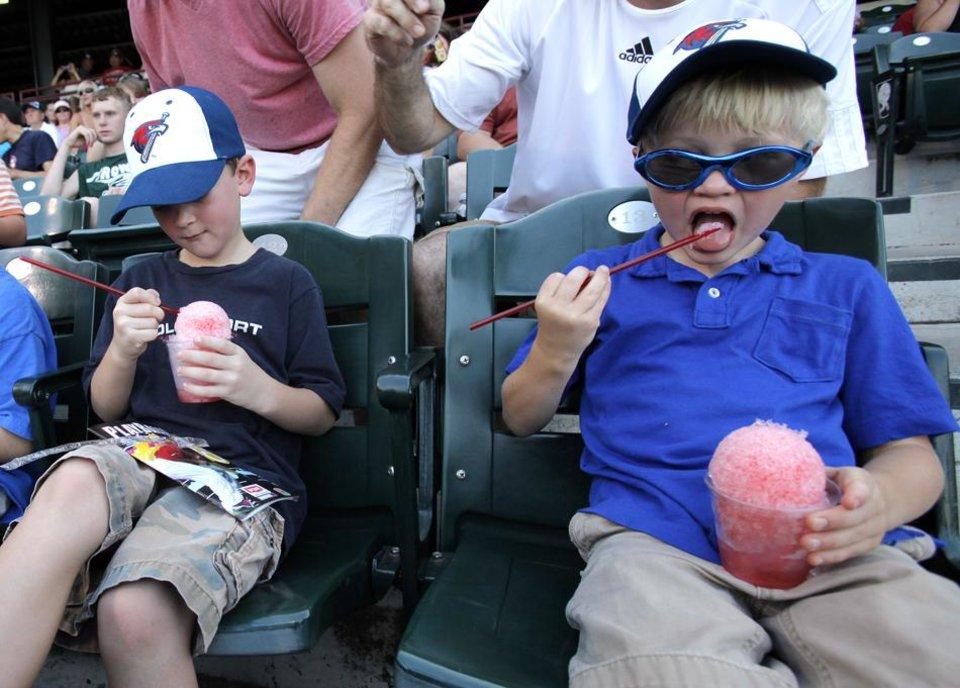 Photo -  Cole Osuburn, 6, and William Shoemaker, 5, enjoy snow cones during a game between the Oklahoma City Redhawks and the Omaha Storm Chasers in Oklahoma City, Saturday, July 9, 2011.  Temperatures in Oklahoma City reached 110 degrees.  Photo by Garett Fisbeck, The Oklahoman ORG XMIT: KOD