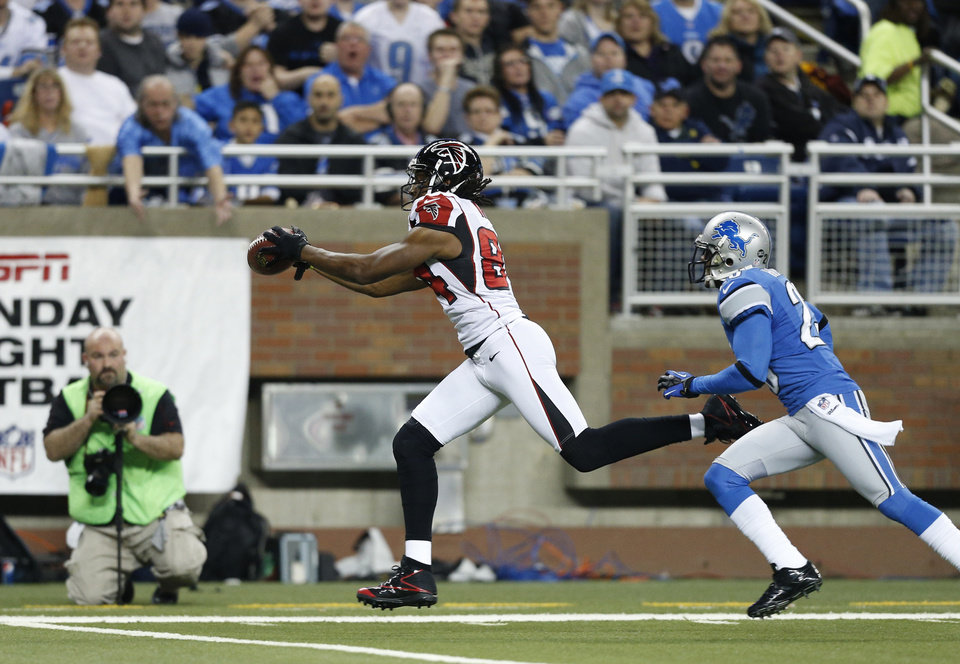 Atlanta Falcons wide receiver Roddy White, defended by Detroit Lions cornerback Chris Houston (23), catches a pass and runs into the end zone for a touchdown during the first quarter of an NFL football game at Ford Field in Detroit, Saturday, Dec. 22, 2012. (AP Photo/Rick Osentoski)