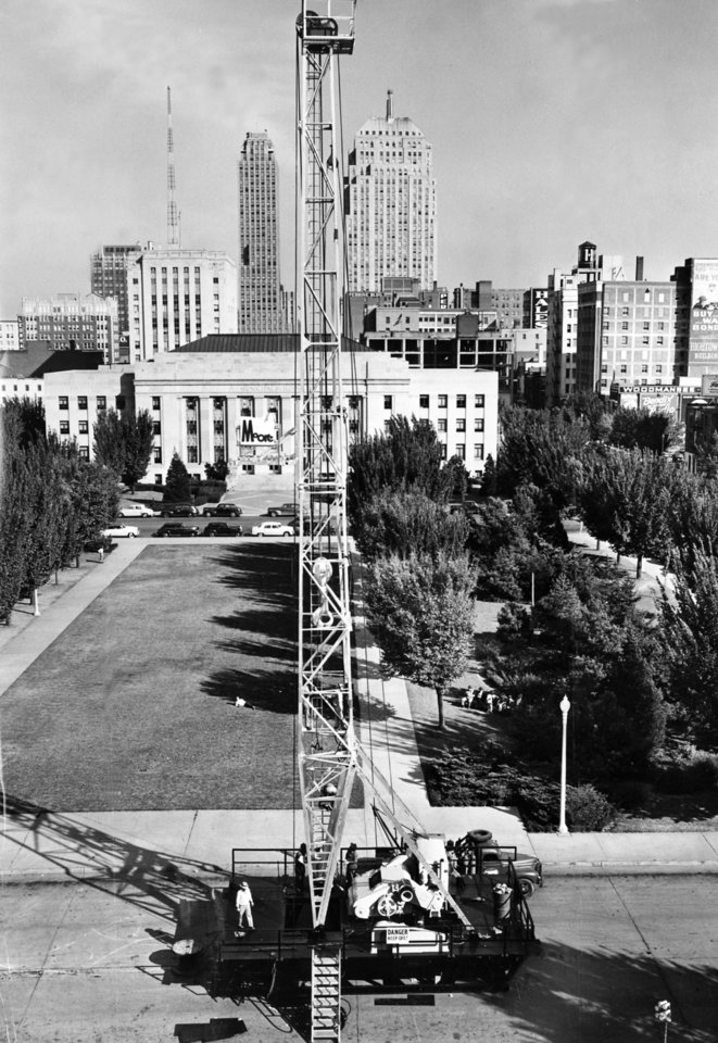 "Photo - ""The oil rig is shown drilling in Civic Center"". Oil rig drilling on Walker Avenue between the Oklahoma City Municipal Building to the east (not shown) and the Municipal Auditorium (Civic Center Music Hall) to the west (shown). Staff photo by Al McLaughlin taken 10/17/1949; photo ran in the 10/18/1949 Daily Oklahoman."