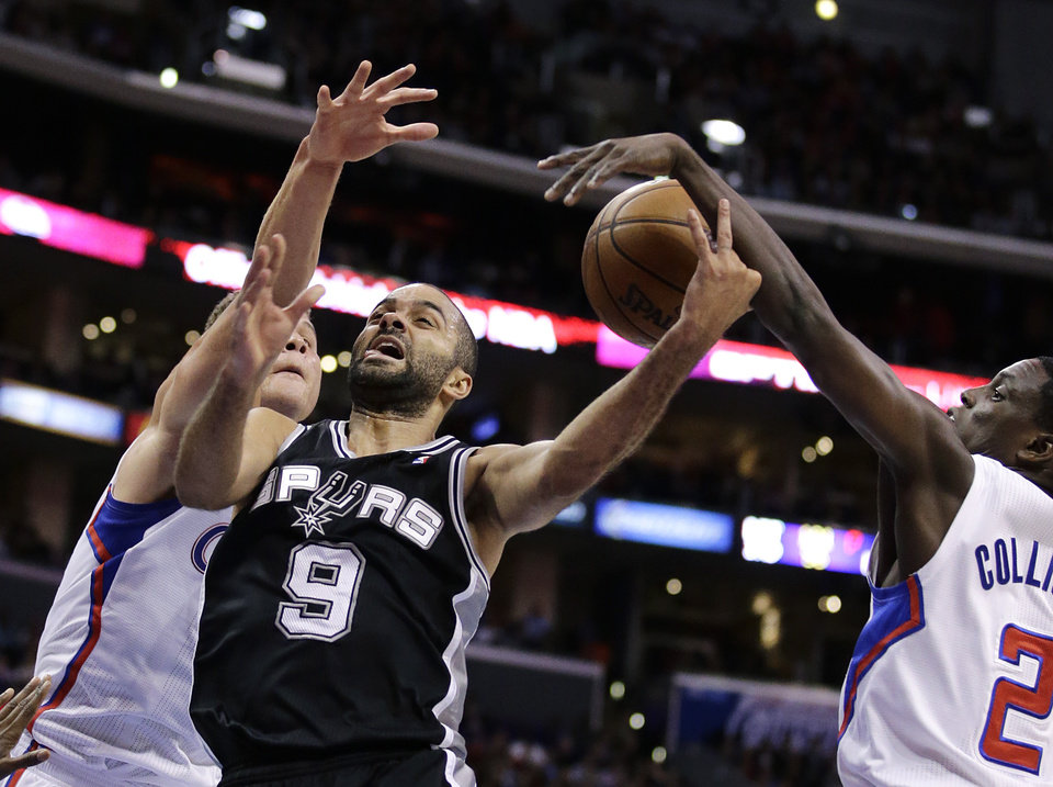 Photo - San Antonio Spurs' Tony Parker, center, of France, is defended by Los Angeles Clippers' Blake Griffin, left, and Darren Collison during the first half of an NBA basketball game on Monday, Dec. 16, 2013, in Los Angeles. (AP Photo/Jae C. Hong)