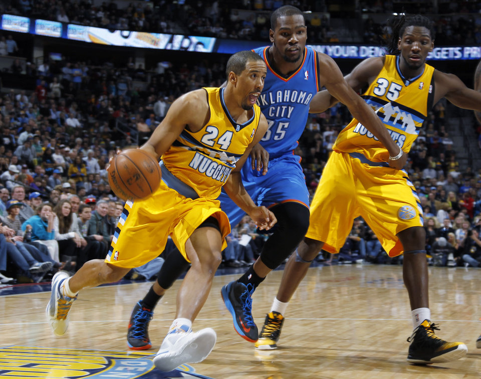 Denver Nuggets guard Andre Miller, left, drives against Oklahoma City Thunder forward Kevin Durant, center, in overtime of an NBA basketball game in Denver on Sunday, Jan. 20, 2013. Nuggets forward Kenneth Faried trails at right. The Nuggets won 121-118 in overtime. (AP Photo/David Zalubowski)