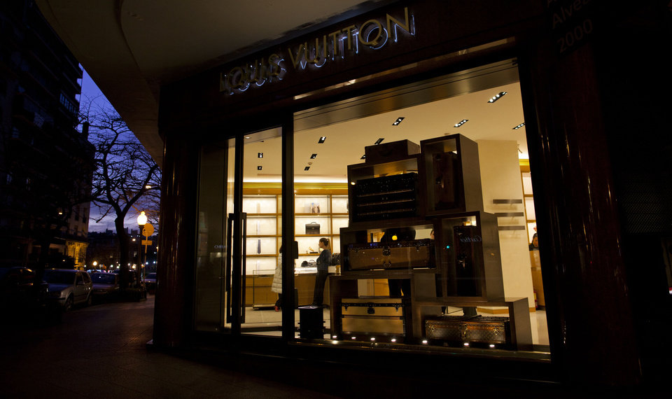 In this Sept. 26, 2012 photo, a vendor stands inside a Louis Vuitton store on Alvear Avenue in the Recoleta neighborhood of Buenos Aires, Argentina. The world's most luxurious designer brands are abandoning Argentina rather than complying with tight new government economic restrictions, leaving empty shelves and storefronts along the capital's elegant Alvear Avenue, where tourists once flocked to see the latest in fashion. (AP Photo/Natacha Pisarenko)