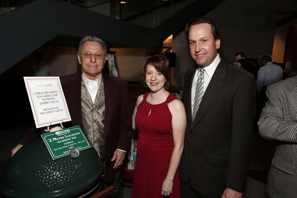 Photo - Gene McKown, Nicole Jarvis Zimmerer, MD, and her husband Jason Zimmerer attend the Winter Gala at the Sam Noble Oklahoma Museum of Natural History on Thursday, Dec. 13, 2012, in Norman, Okla.  Photo by Steve Sisney, The Oklahoman