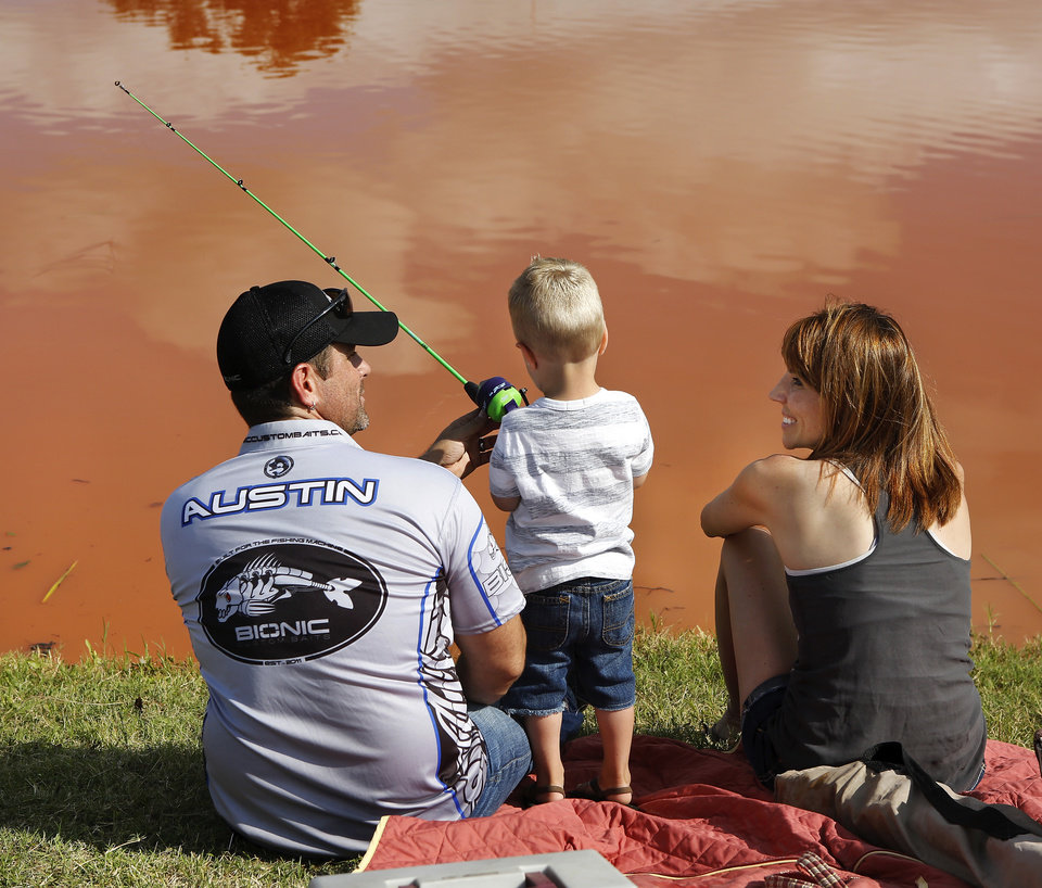 Photo - Stephen Austin and his wife, Chainey, and their son, Cooper, 2, try their luck fishing with others at the derby.   Stephen Austin owns Bionic Custom Baits in Yukon, and he came as a volunteer to help children with their fishing techniques. Moore hosted its annual kids fishing derby Saturday morning, July 27, 2013,  at Buck Thomas Park.  As part of the event this year, a charity called the Tackle the Storm Foundation handed out rods and reels to tornado victims. Several bass fishing pros from Oklahoma attended the event to help distribute the fishing equipment and share fishing tips with the young anglers. An event official  said about 250 children participated in the fishing derby. Photo  by Jim Beckel, The Oklahoman.