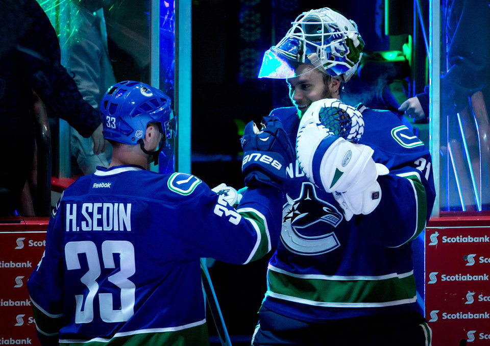 Photo - Vancouver Canucks' Henrik Sedin, left, and goalie Eddie Lack, both of Sweden, celebrate their 2-0 win over the Nashville Predators during an NHL hockey game in Vancouver, British Columbia, on Wednesday, March 19, 2014. (AP Photo/The Canadian Press, Darryl Dyck)