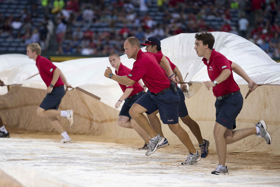 Photo - Atlanta Braves grounds crew members race to cover the infield before a downpour that delayed the start of the Braves' baseball game against the Washington Nationals on Saturday, Aug. 9, 2014, in Atlanta. (AP Photo/John Bazemore)