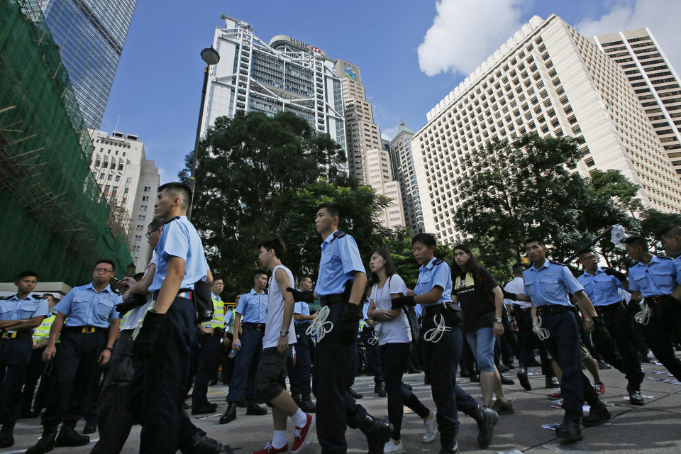 Photo - Arrested protesters are escorted out by police officers outside HSBC headquarters in the financial district in Hong Kong Wednesday, July 2, 2014, following a huge rally to show their support for democratic reform and oppose Beijing's desire to have the final say on candidates for the chief executive's job. More than 500 protesters were arrested from sit-in during pro-democracy rally. (AP Photo/Vincent Yu)