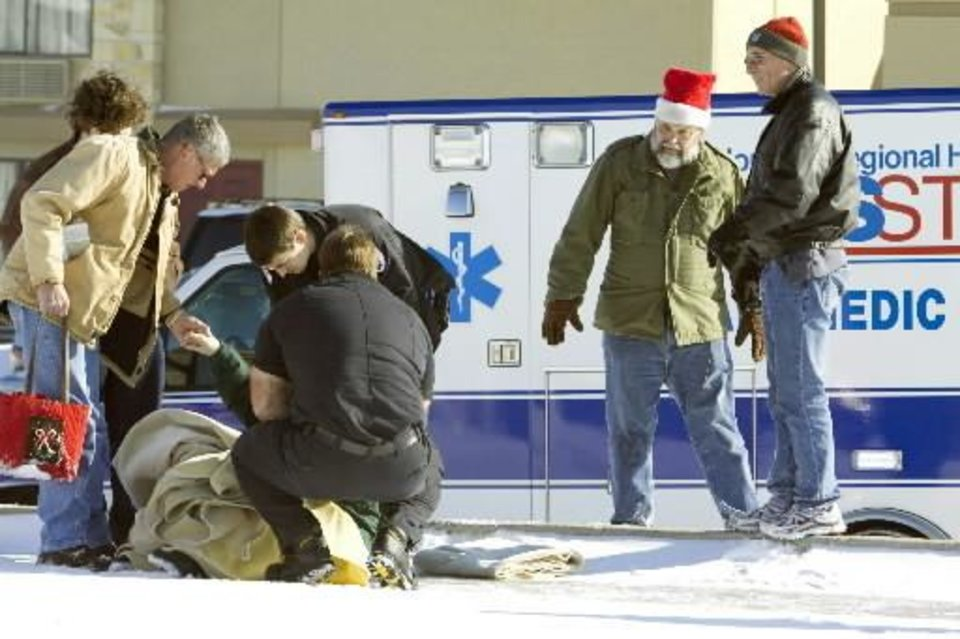 Norman emergency workers tend to an inidentified woman who fell on ice near Interstate Drive and Main on Christmas Day on Friday, Dec. 25, 2009, in Norman, Okla. The woman was transported to a local hospital. Photo by Steve Sisney