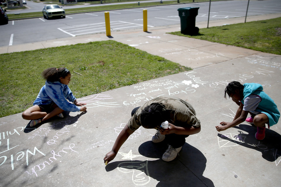 Photo - From left, Kyirah Velasco, 10, La'Niyah Morgan, 10, and Ava Hodge, 7, add to chalk drawings on the sidewalk outside the Schilling Recreation Center in Oklahoma City on March 26. They were attending a day camp for the children of city of Oklahoma City employees. [Bryan Terry/The Oklahoman]