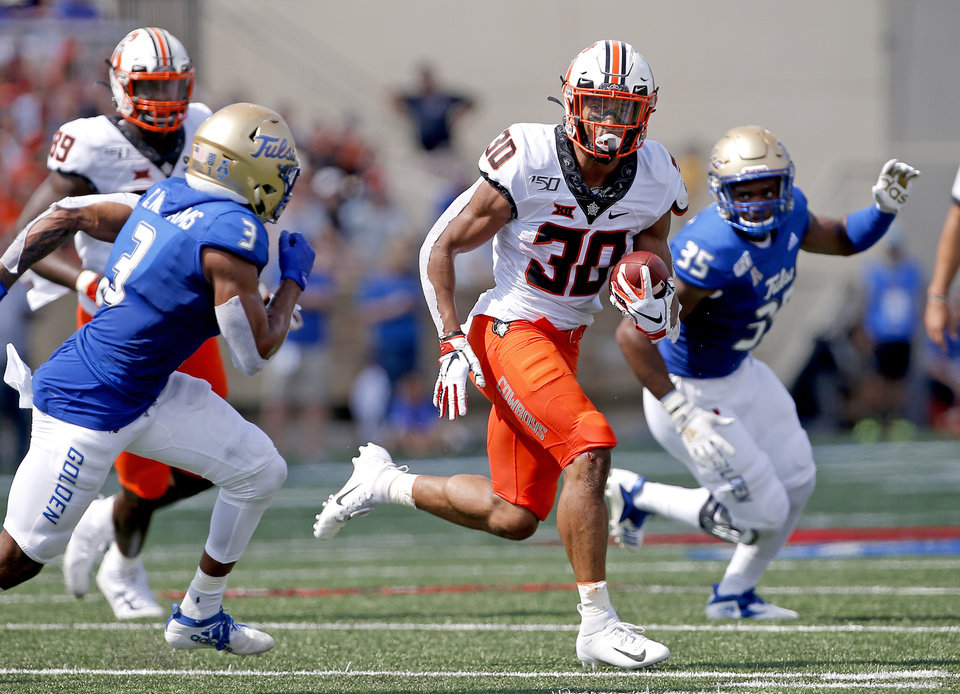 Photo - Oklahoma State's Chuba Hubbard (30) rushes in the first quarter as Tulsa's Cristian Williams (3) and Yohance Burnett (35) defend during a college football game between the Oklahoma State University Cowboys (OSU) and the University of Tulsa Golden Hurricane (TU) at H.A. Chapman Stadium in Tulsa, Okla., Saturday, Sept. 14, 2019. [Sarah Phipps/The Oklahoman]