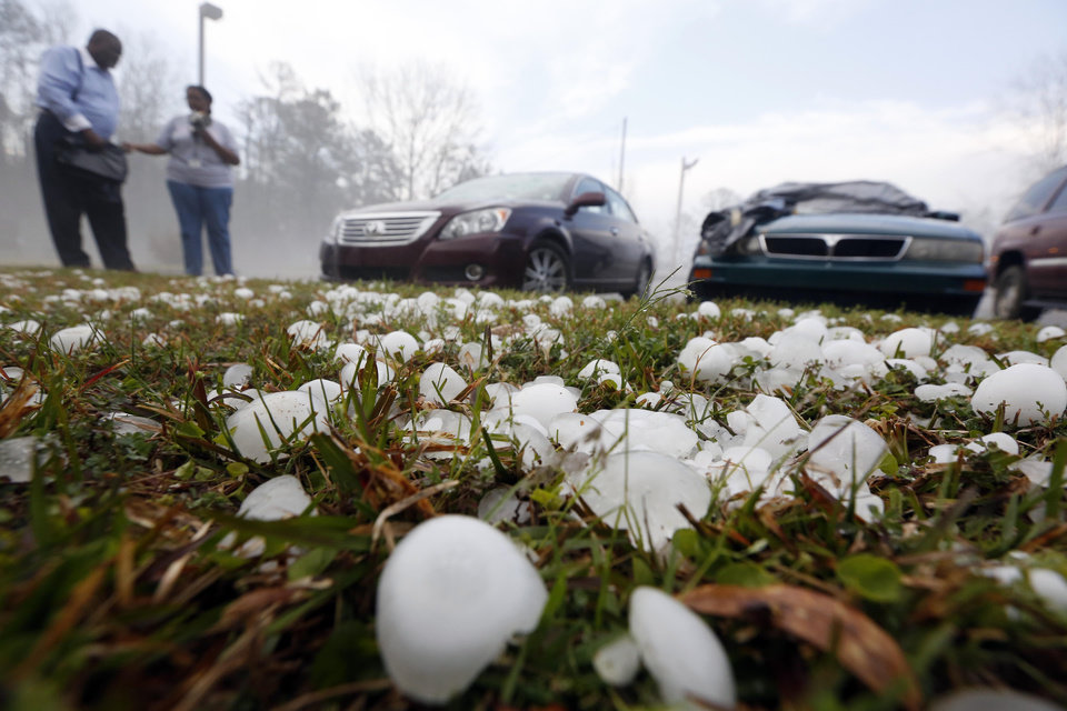 Photo - Golfball sized hail litter the ground by  Andrew Stamps and his wife Valorie as they prepare to cover their shattered rear window of her 2009 Toyota Avalon in Pearl, Miss., Monday, March 18, 2013, following a hailstorm that hit communities throughout central Mississippi. The National Weather Service in Jackson says there were a few super cells in central Mississippi and reports of hail up to baseball size in Clinton, golf ball and tennis ball sized in Pearl and Brandon and quarter sized in downtown Jackson, Miss. The Mississippi Emergency Management Agency says severe weather has caused damage in at least 10 counties as the storms moved through parts of the state. (AP Photo/Rogelio V. Solis)