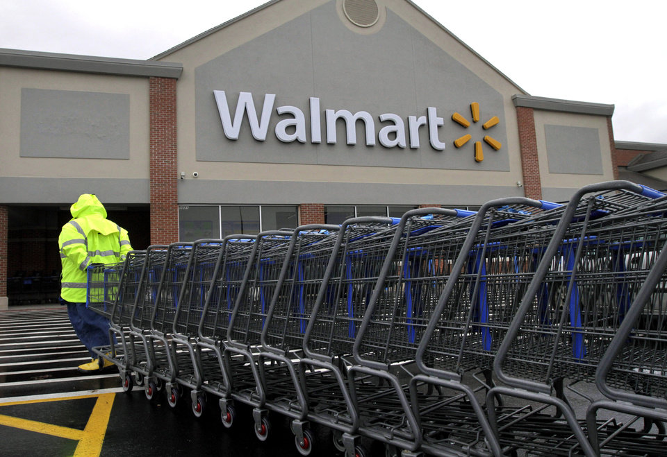 In this Tuesday, Nov. 13, 2012 photo a worker pulls a line of shopping carts toward a Walmart store in North Kingstown, R.I. Wal-Mart Stores Inc. reported a 9 percent increase in net income for the third quarter, but revenue for the world\'s largest retailer fell below Wall Street forecasts as its low-income shoppers continue to grapple with an uncertain economy. (AP Photo/Steven Senne)