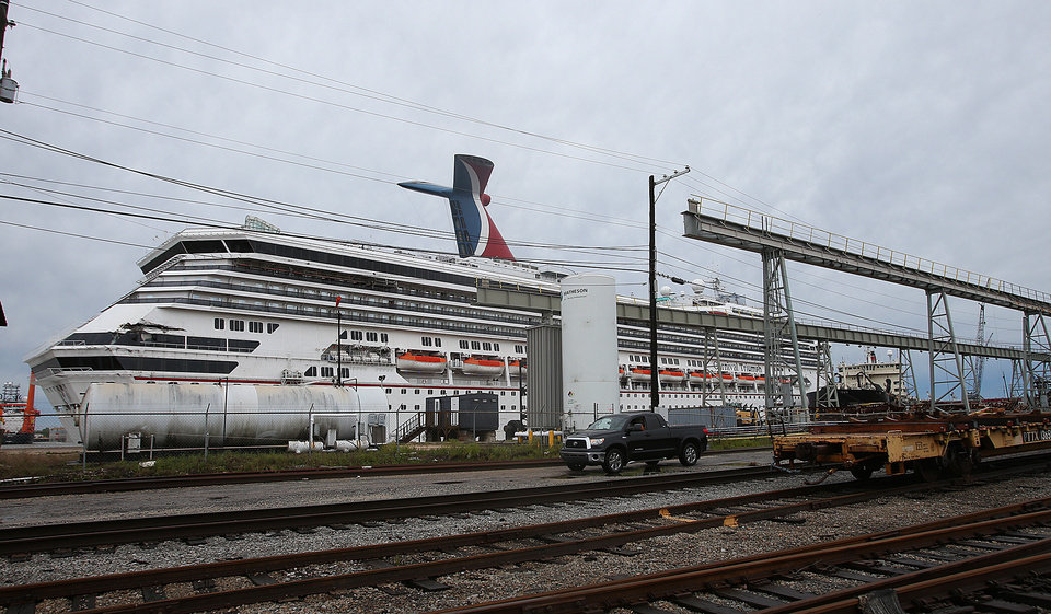 Photo - The Carnival cruise ship Triumph rests against a dock on the east side of the Mobile River after becoming dislodged from its mooring at BAE Shipyard during high winds Wednesday, April 3, 2013 in Mobile, Ala. Triumph was disabled Feb. 10 by an engine fire that stranded thousands of passengers onboard for days in the Gulf. It was towed into port in Mobile. (AP Photo/AL.com, Bill Starling)  MAGS OUT