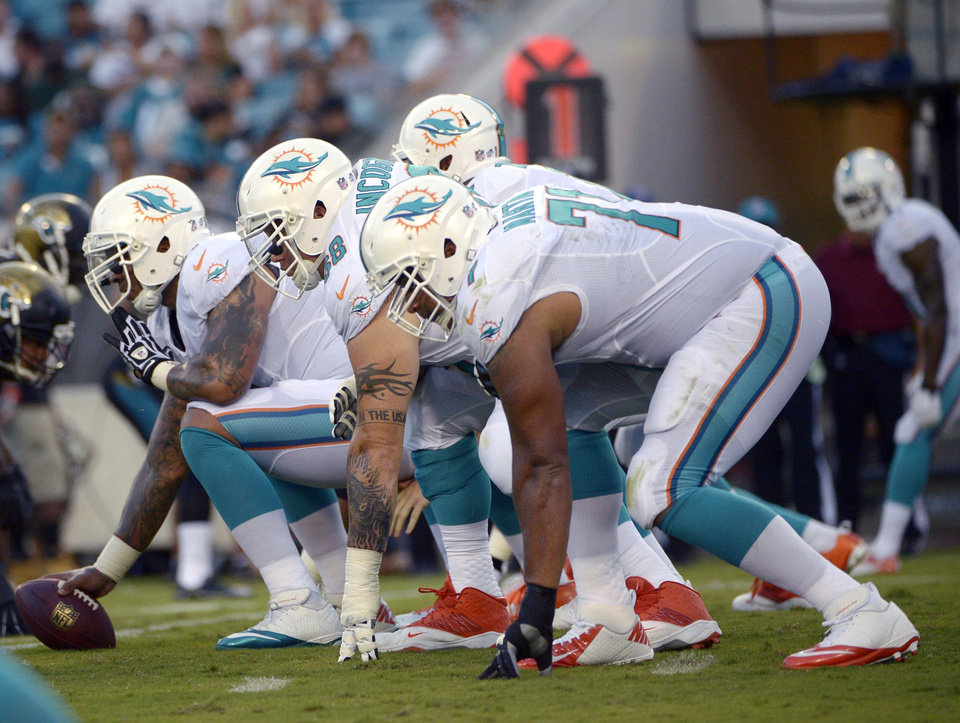 Photo - FILE - In this Aug. 9, 2013, file photo, Miami Dolphins center Mike Pouncey, left, guard Richie Incognito (68) and tackle Jonathan Martin (71) set up to block during the first half of an NFL preseason football game against the Jacksonville Jaguars in Jacksonville, Fla. Martin was subjected to