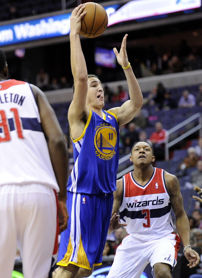 Golden State Warriors guard Klay Thompson (11) goes to the basket against Washington Wizards guard Bradley Beal (3) and Chris Singleton (31) during the first half of an NBA basketball game, Saturday, Dec. 8, 2012, in Washington. (AP Photo/Nick Wass)