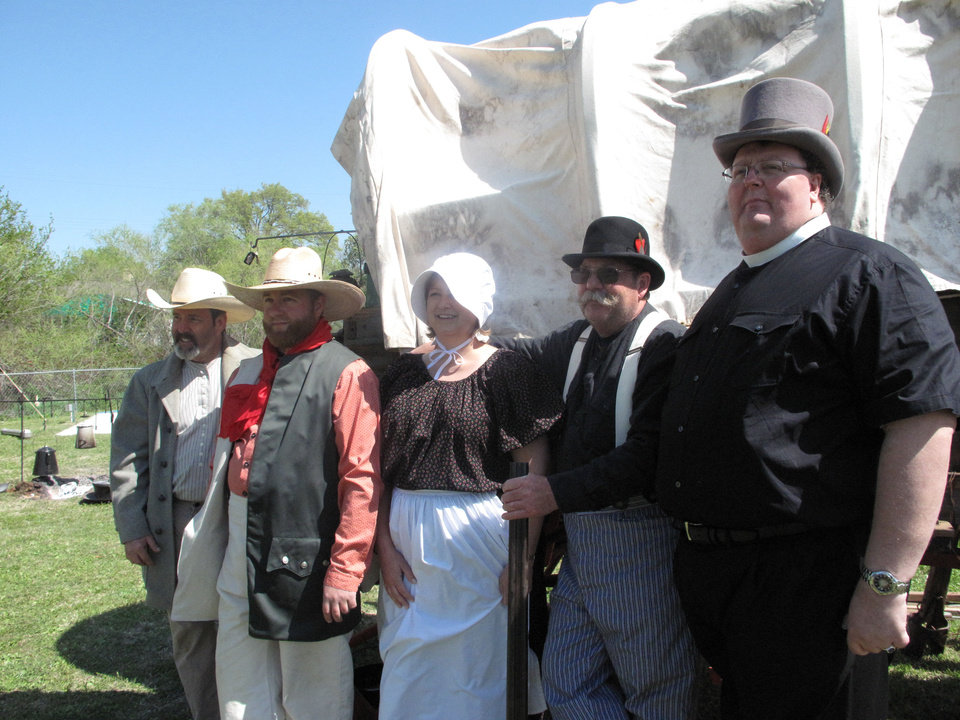 Photo - Several members of First Christian Church of Oklahoma City (Disciples of Christ) pose for a photo near a covered wagon displayed as part of the church's 124th anniversary service April 21 at 3700 N Walker. Photo provided by Carla Hinton, The Oklahoman