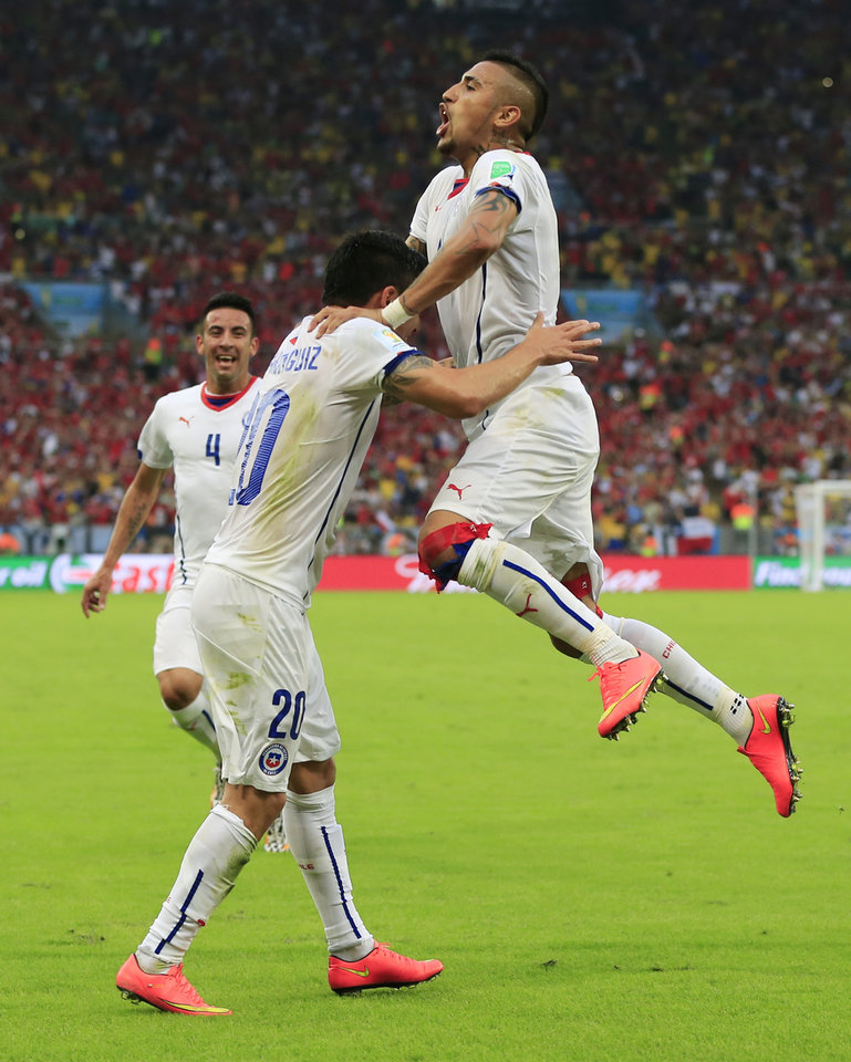 Photo - Chile's Charles Aranguiz, left, celebrates after scoring his side's second goal during the group B World Cup soccer match between Spain and Chile at the Maracana Stadium in Rio de Janeiro, Brazil, Wednesday, June 18, 2014.  (AP Photo/Bernat Armangue)