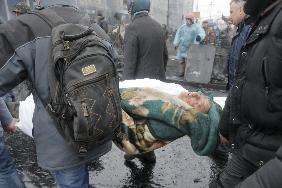Photo - Activists evacuate a protester killed during clashes with police in Kiev's Independence Square, the epicenter of the country's current unrest, Kiev, Ukraine, Thursday, Feb. 20, 2014. Fierce clashes between police and protesters in Ukraine's capital have shattered the brief truce Thursday and an Associated Press reporter has seen dozens bodies laid out on the edge of the protest encampment.  (AP Photo/Efrem Lukatsky)