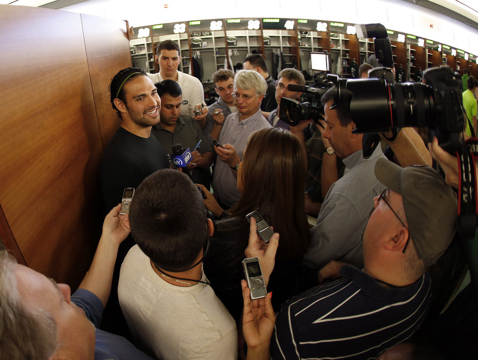 Photo - In this image taken with a fisheye lens,New York Jets quarterback Mark Sanchez, left, talks to reporters during a locker room availability at the team's NFL practice practice facility in Florham Park, N.J., Thursday, May 2, 2013. The Jets may have cut Tim Tebow but their situation at quarterback is far from settled. New general manager John Idzik says Sanchez, David Garrard, Greg McElroy, Matt Simms and second-round draft pick Geno Smith are all candidates to be the starter. (AP Photo/Rich Schultz)