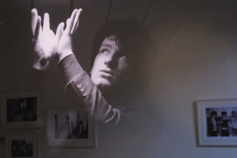 "With other photos reflected behind, a February 1979 photo of an 18-year-old Bono posing under a fluorescent light is one of the more striking images from the ""U2 1978-1981""' exhibition opening in Dublin. The Little Museum of Dublin is displaying a collection of pictures by photographer Patrick Blocklebank, documenting the gritty beginnings of U2 in the smoky pubs and clubs of Dublin before the Irish band became the international rock band of today. AP PHOTOS"