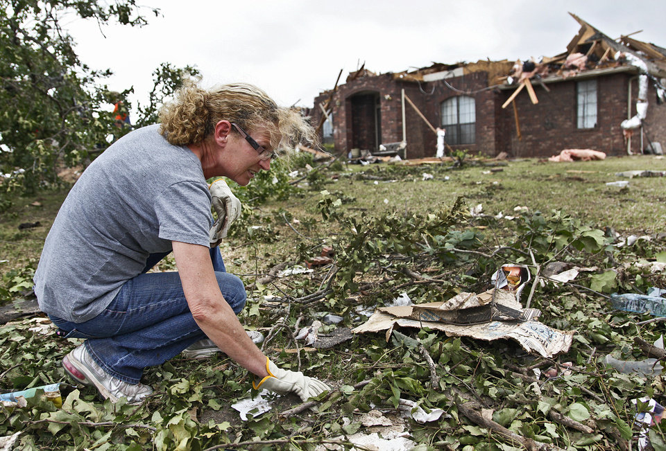Homeowner Donna Hensley gathers personal belongings scattered in the debris on Wednesday, May 12, 2010, in Oklahoma City, Okla. Hensley\'s home was destroyed by the tornados that hit central oklahoma on Monday. Photo by Chris Landsberger, The Oklahoman