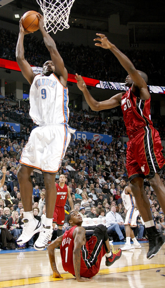 Photo - Oklahoma City's Serge Ibaka goes to the basket over Miami's Dorell Wright and Joel Anthony during the NBA basketball game between the Oklahoma City Thunder and the Miami Heat at the Ford Center in Oklahoma City, Saturday, January 16, 2010. Photo by Bryan Terry, The Oklahoman