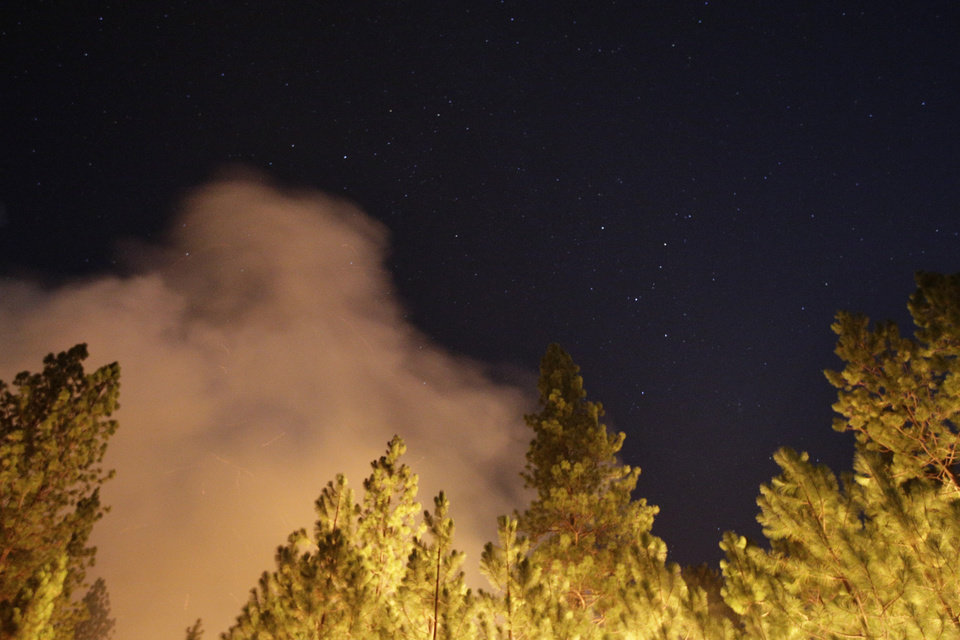 Photo - The smoke generated by the Rim Fire rises under a star-filled sky near Yosemite National Park, Calif., on Sunday, Aug. 25, 2013. Fire crews are clearing brush and setting sprinklers to protect two groves of giant sequoias as a massive week-old wildfire rages along the remote northwest edge of Yosemite National Park. (AP Photo/Jae C. Hong)