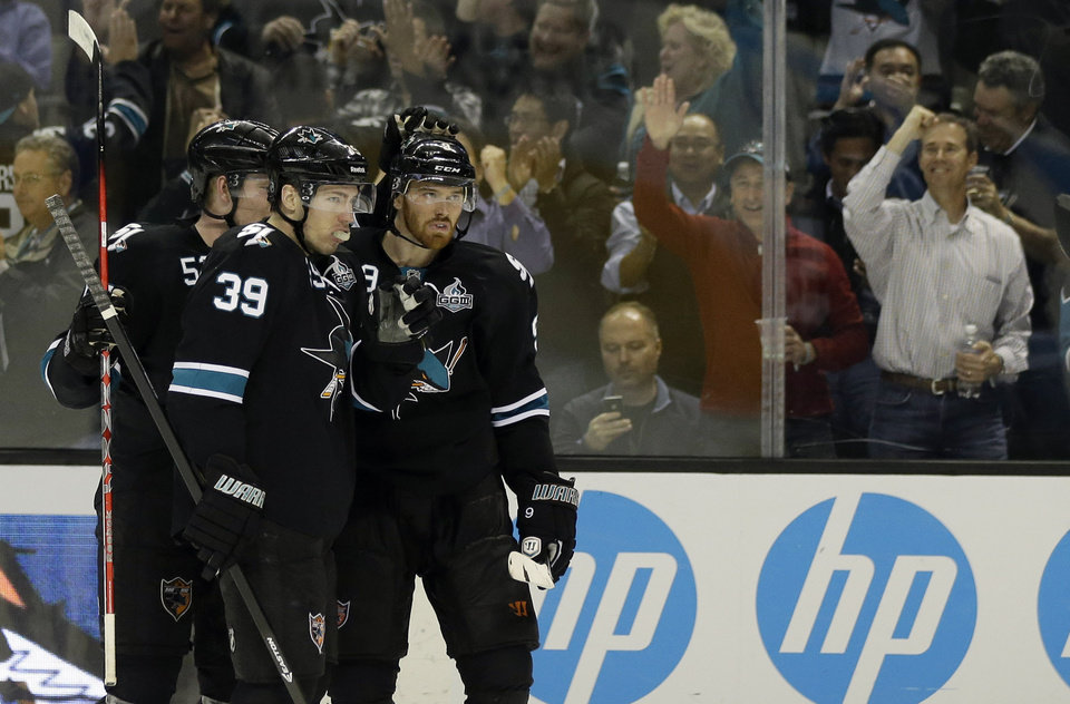 Photo - San Jose Sharks center Logan Couture (39) celebrates with teammates after scoring against the Minnesota Wild during the third period of an NHL hockey game in San Jose, Calif., Thursday, April 18, 2013. (AP Photo/Marcio Jose Sanchez)